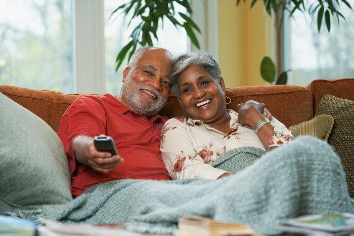 A man and a woman sitting together on a couch and smiling