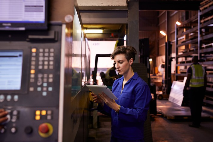 A factory worker holding a tablet standing next to manufacturing equipment.