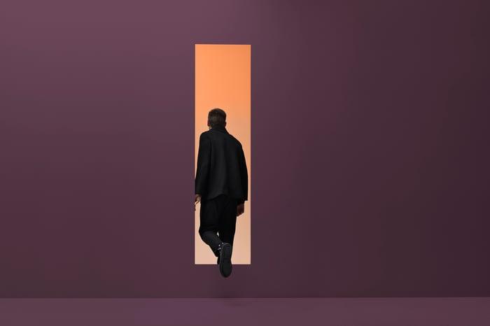 Man walking threw rectangular opening in colored room