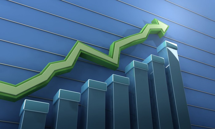 A green up arrow representing a rising stock market chart.