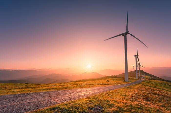 Éoliennes le long d'une route avec le soleil qui se couche en arrière-plan.