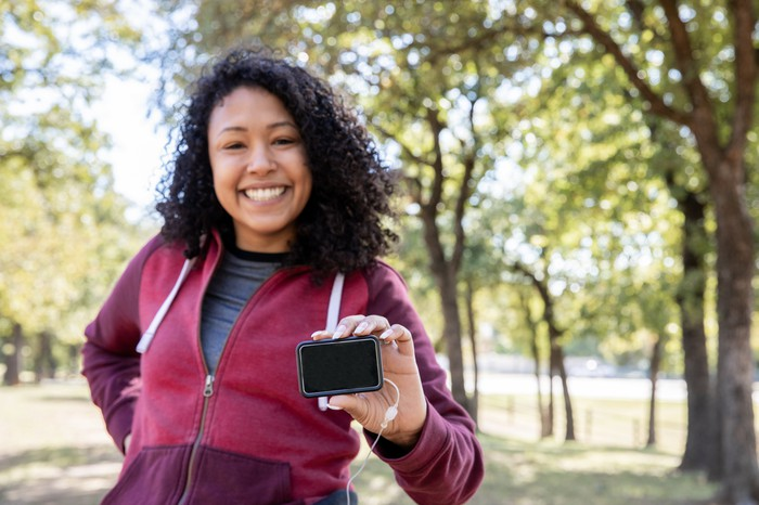 Woman jogging with continuous glucose monitor.