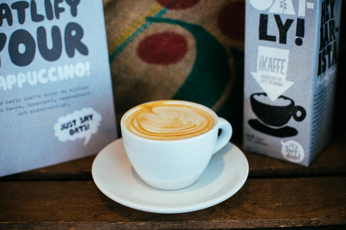 Oatly products surrounding a cup of designer coffee.