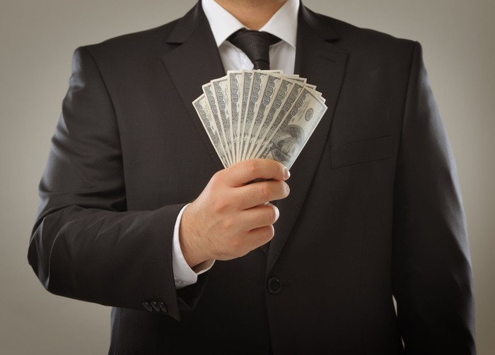 man holding $1000 in cash