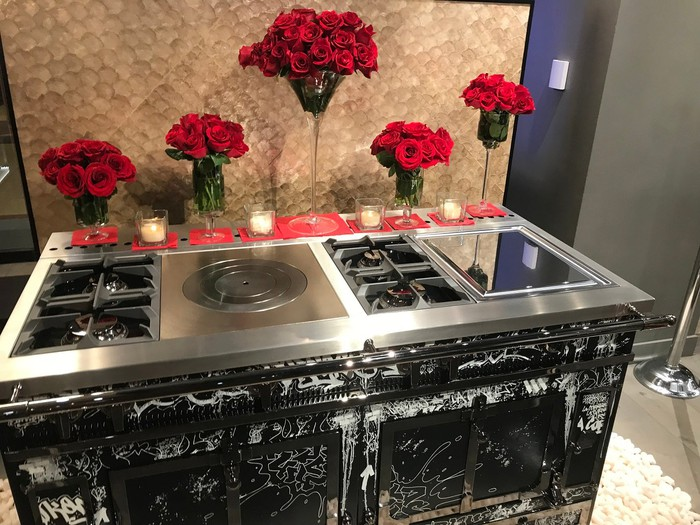 A stove with twin ovens in front of flower arrangements and with votive candles along the rear edge.