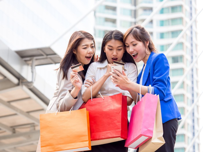 Three women holding shopping bags and credit cards and looking excitedly at a cellphone one of them is holding