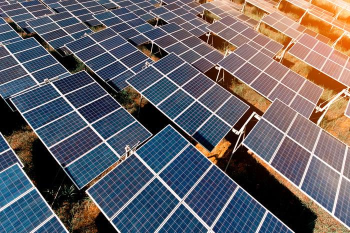 Plusieurs rangées de panneaux solaires installés dans une ferme solaire.