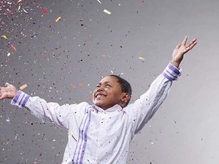 A child celebrates as confetti rains down.