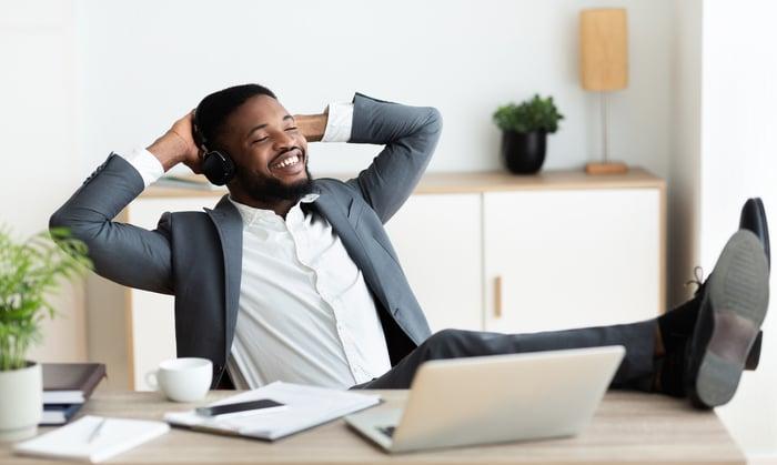homme assis en arrière et souriant à son bureau