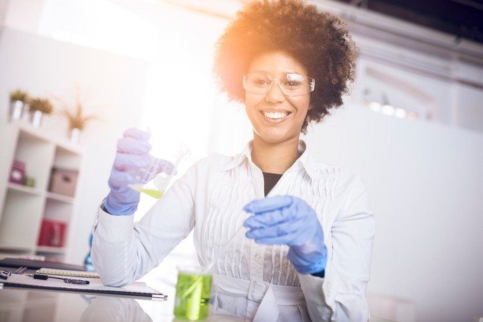 Smiling scientist holds beakers in a lab.