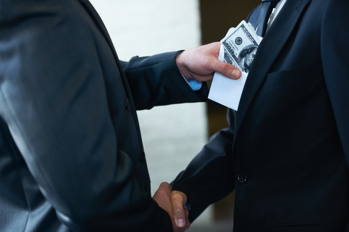 Two businessmen shaking hands with one stuffing an envelope of money into the front of the other's suit.