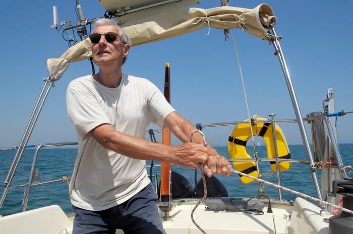 Older man pulling rope on a boat
