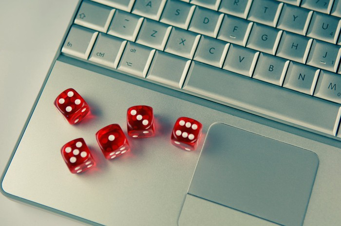Five red dice on a silver laptop computer keyboard.