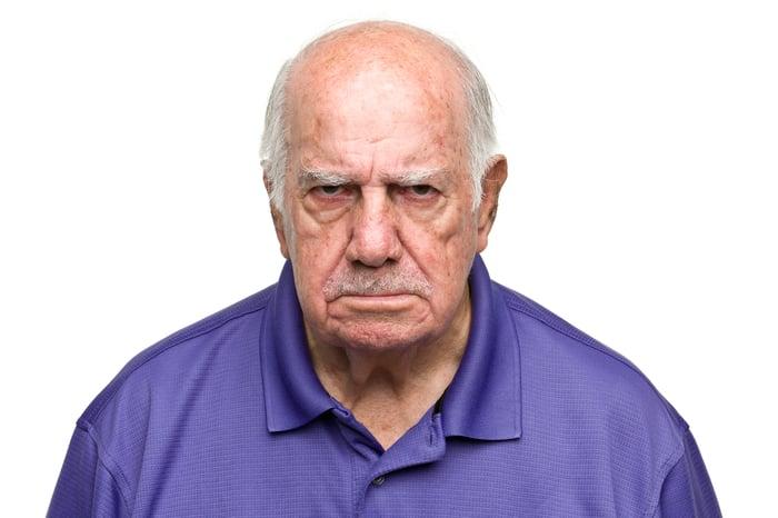 Elderly man frowning.