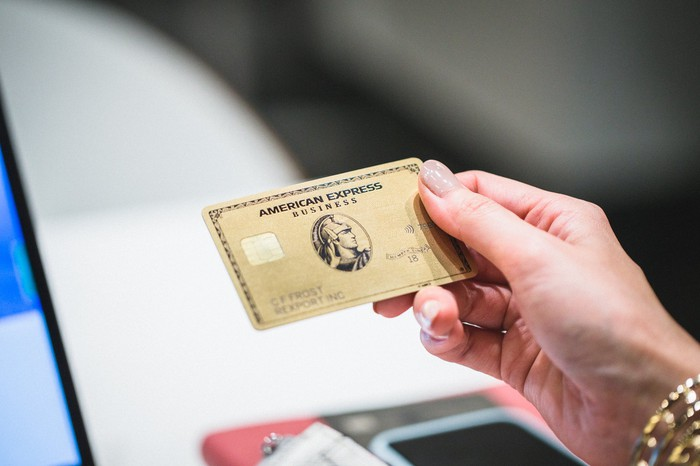 A person holding an American Express gold business card in their right hand.