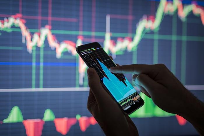 Une personne utilisant son smartphone pour consulter un graphique boursier très volatil.