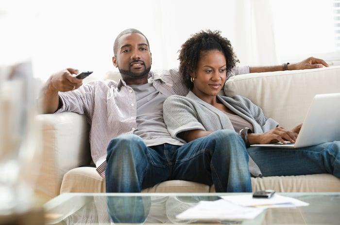 Un couple assis sur un canapé.  Il a une télécommande à la main alors qu'il regarde une télévision, et elle regarde un ordinateur portable.