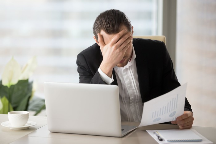 A man holding his head looking at a paper.