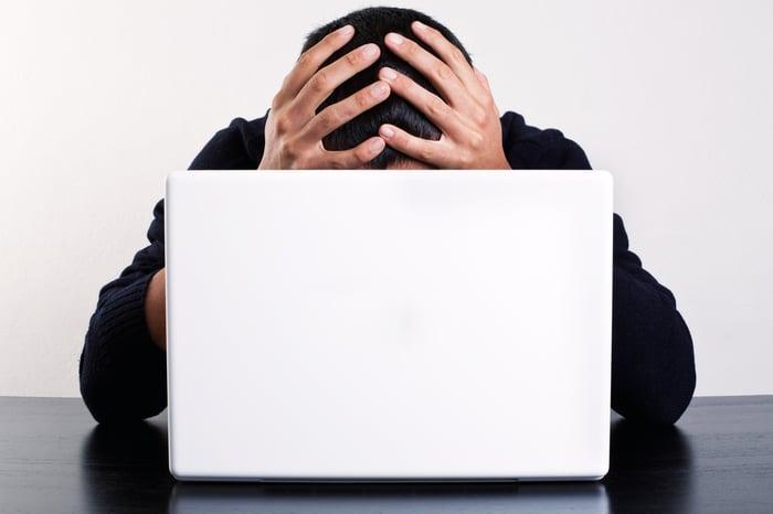 Homme à l'ordinateur portable tenant sa tête