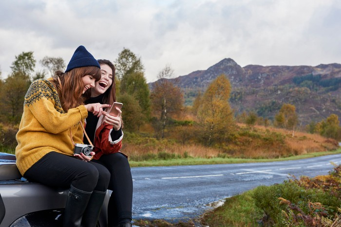 Two women laugh at something on their smartphones by a road out in the country on a cloudy day.