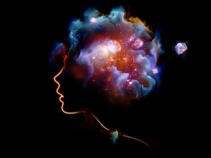 Creative art displaying the profile of human face with colorful nebulae inside the head.