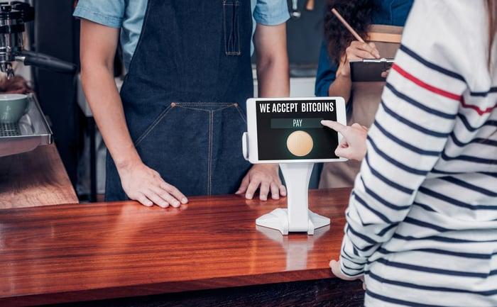 Un appareil de point de vente à un comptoir de caisse qui lit, Nous acceptons les Bitcoins.