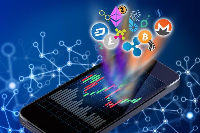 Un smartphone affichant un graphique en chandeliers avec divers logos de crypto-monnaie rayonnant du graphique.