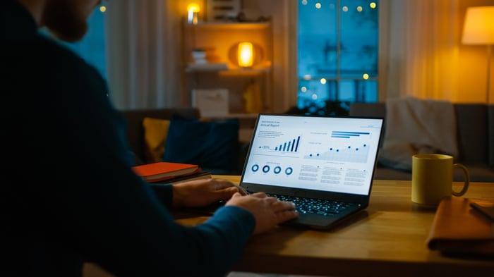 Un homme à la recherche de graphiques sur son ordinateur portable