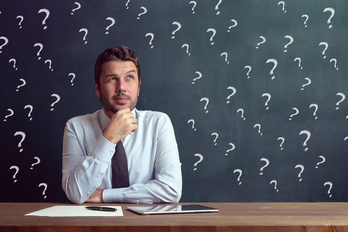 A man sits at a desk in front of a chalkboard with question marks.