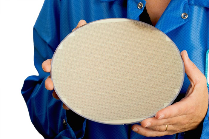 Man holds a circular semiconductor wafer in his hands.