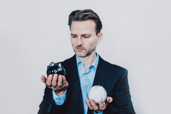 A person holding a black piggy bank in one hand and a white piggy bank in the other.