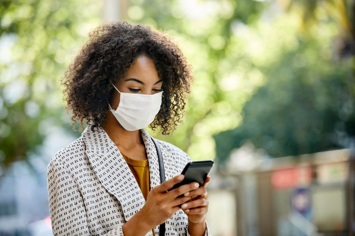 A woman wearing a mask and looking at her phone.