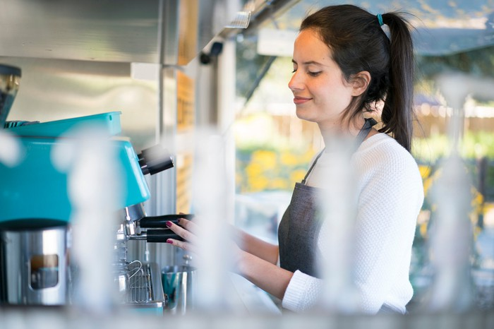 Lady barista smiling while preparing a cup of coffee at a coffee machine