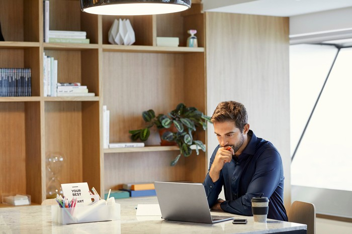 Man in casual clothes sitting in a large office, regarding a laptop thoughtfully