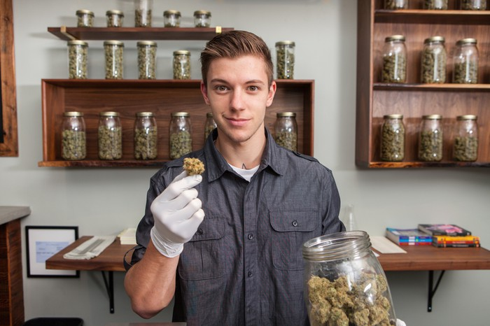 Man holding a jar of dried cannabis in a dispensary shop.