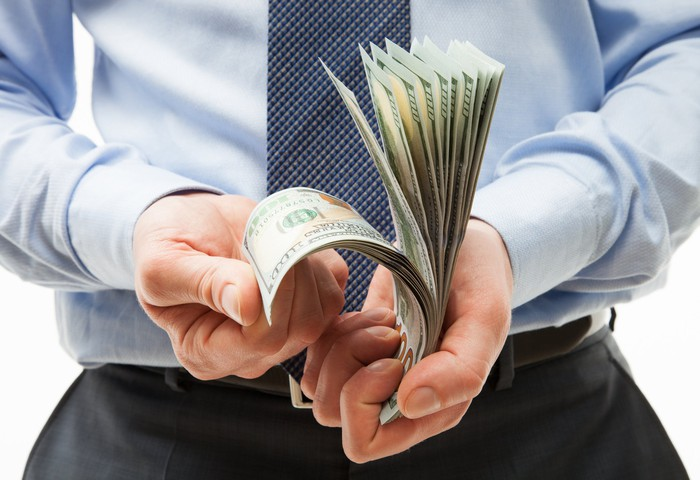 A businessman rifling through a stack of one hundred dollar bills in his hands.