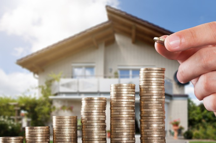 Ascending stacks of coins in front of a two-story residential home.