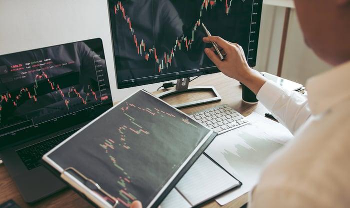 Man sitting at a computer desk analyzing stock charts.