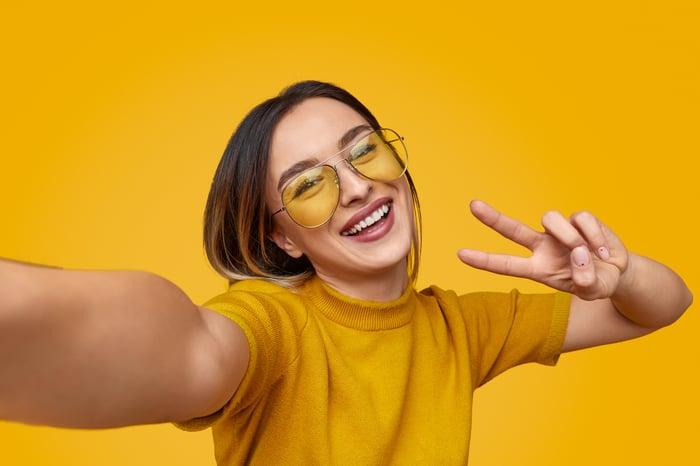 A smiling woman takes a selfie.