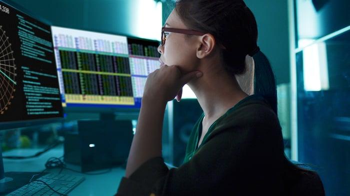 Woman studying financial market information on desktop.