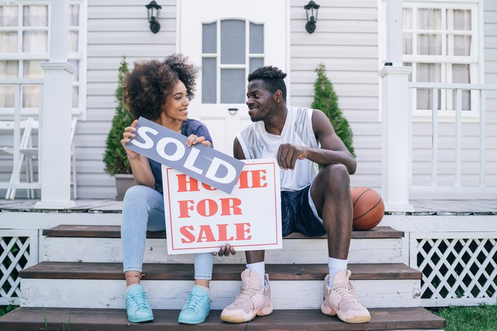 """Two happy people sitting on the steps of their porch holding """"For Sale"""" and """"Sold"""" signs."""