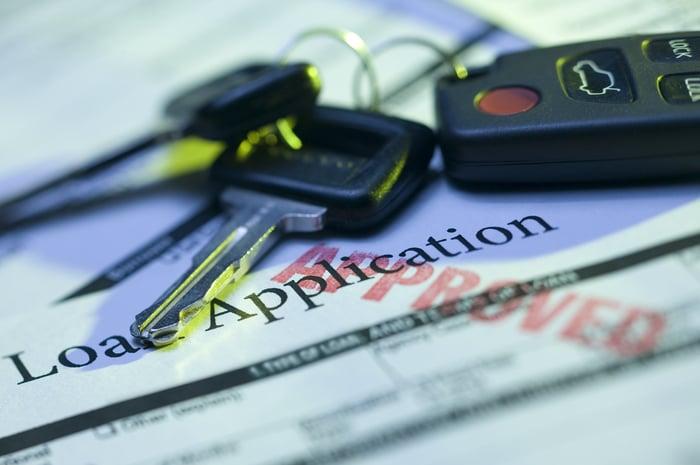 Keys sit on top of auto loan application.