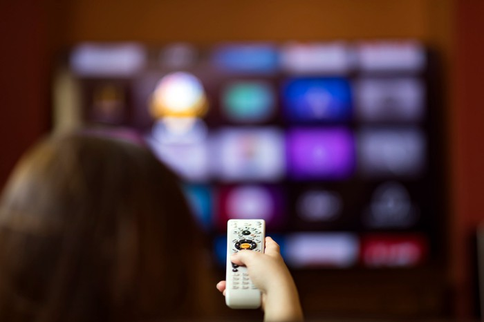 A person points a remote control at a TV that is blurry in the background.