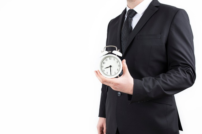 A businessman holds an alarm clock in one hand.
