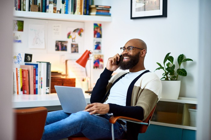 Man sits at his desk while speaking on the phone with his laptop on his lap.