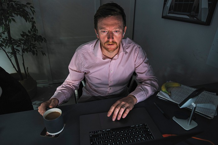 Man with a coffee cup in his hand and a worried expression on his face in a dark room, sitting and looking at his laptop
