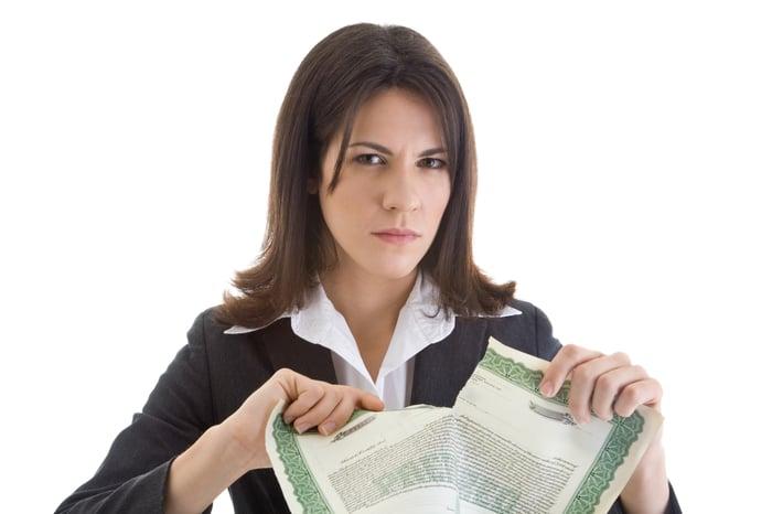Une femme déchire un certificat d'actions en deux.