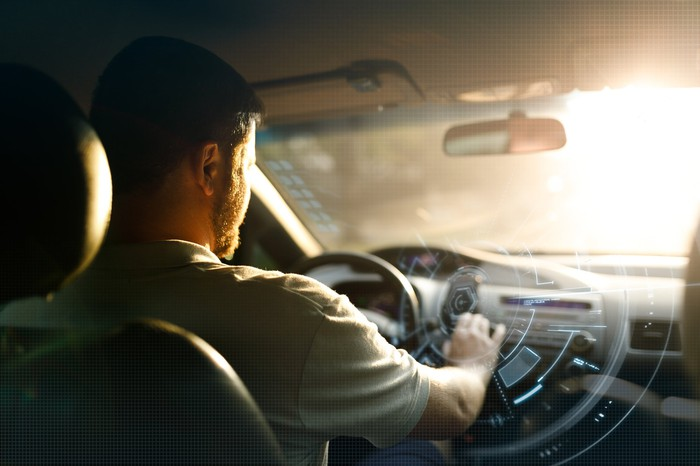 A man accesses digital services on his vehicle's dashboard.