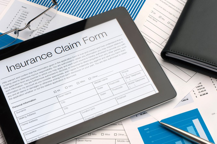 A tablet with an digital insurance claim form sits on a pile of paperwork