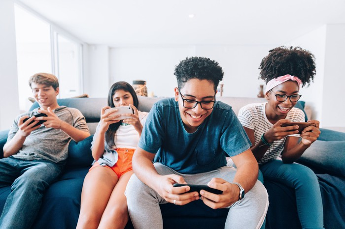 A group of friends plays smartphone games together.